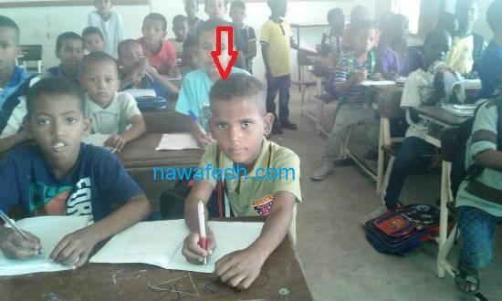 في مقدمة الصف يبدو التلميذ وفي يده اليمنى القلم الذي أهداه الرئيس